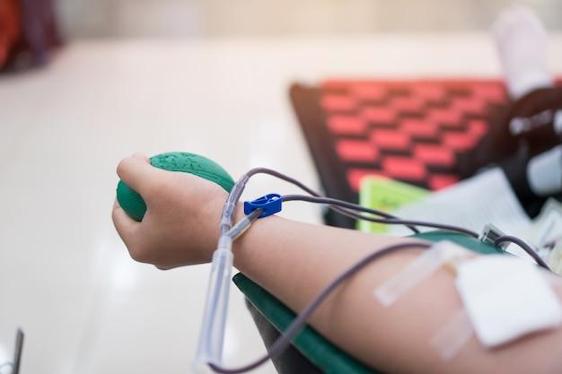 건강 및 의료, 수혈 헌혈자 기부 바늘이 팔의 정맥을 관통합니다. 사람 기부 자원 봉사자에서 인간 환자에 기여합니다. 다양한 의학적 상태를 대체하는 데 사용