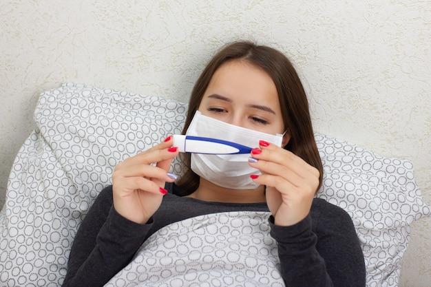 健康と医学。若い女の子は自宅のベッドで病気で、体温計を持っています。