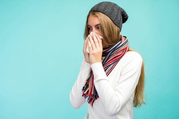 Концепция здоровья и медицины - грустная девушка сморкается в ткани, на синем фоне