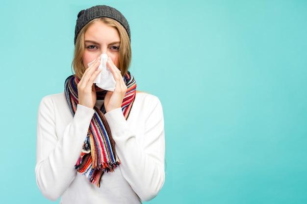 健康と医学の概念-青い空間で、組織に鼻を吹く悲しい十代の少女。鼻水で冷たいかわいい女の子。