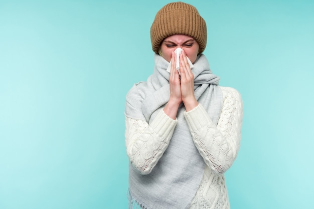 Концепция здоровья и медицины - молодая женщина сморкается в ткани на синем фоне