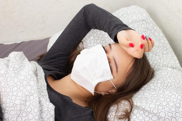 健康と医学。若い女の子はベッドで自宅で病気で、抗ウイルスマスクに横たわっています