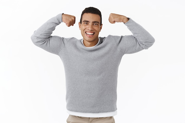 Здоровье и спорт. счастливый веселый улыбающийся молодой спортивный человек, сгибает бицепсы и смеется, становясь сильным