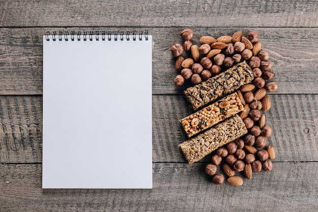 Health bars, mixed nuts and empty notebook blank for text. energy bars with almond and hazelnuts
