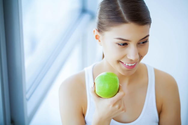 Health and beauty. beautiful young girl with white teeth holding hands of fresh green apple. a woman with a beautiful smile. tooth health