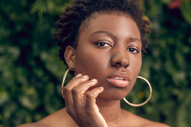 Health, beauty. close up face of young adult well-groomed black woman with short hair looking pensive touching hand to face