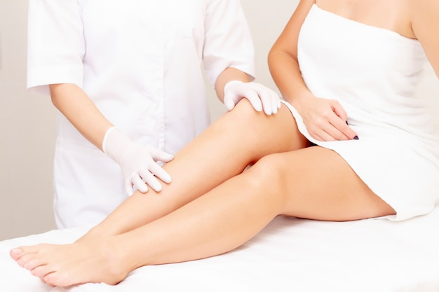 Health and beauty concept, beautiful slim woman in a white towel sits on a white couch. there is a master of depilation, a masseur, a beauty specialist in white gloves and a white coat.
