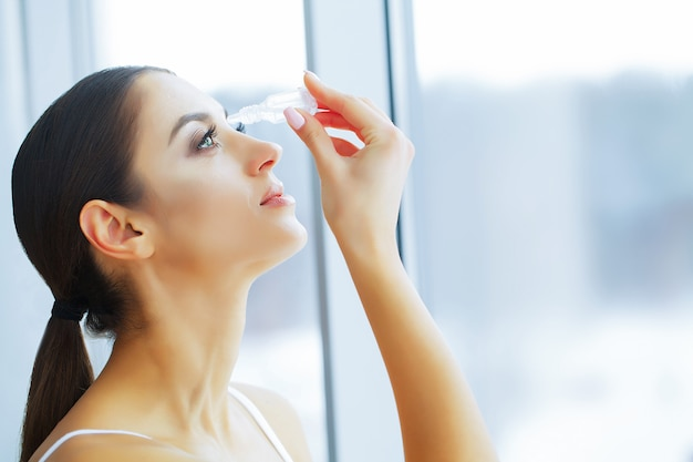 Health and beauty. eye care. beautiful young woman holding drops