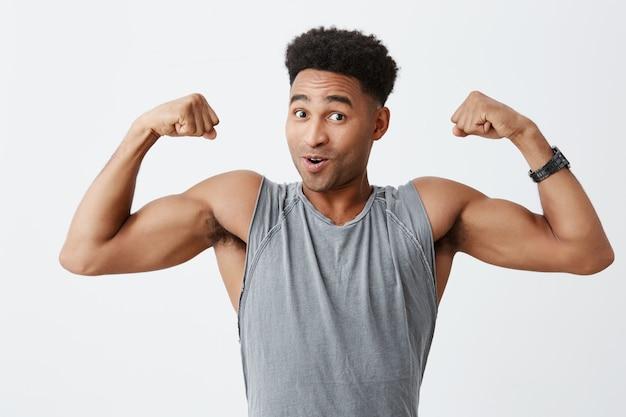 Salute e bellezza. ritratto del maschio africano dalla pelle nera attraente maturo con capelli ricci in camicia grigia sportiva che mostra i muscoli del braccio, guardando a porte chiuse con espressione faccia eccitata.