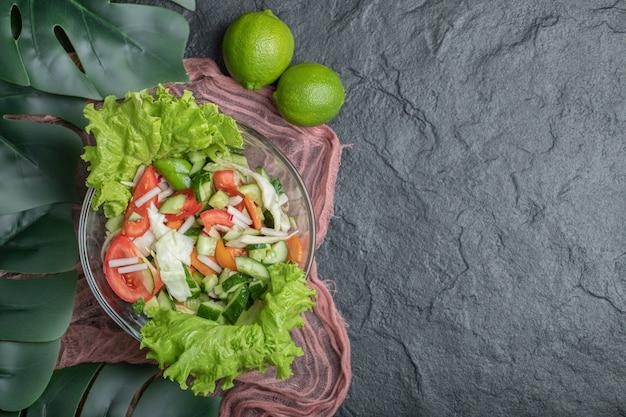 健康と美しさ。黒の背景に野菜サラダとライム。高品質の写真