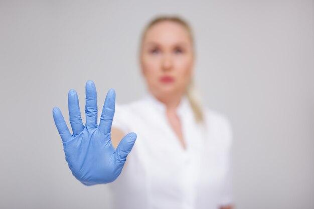 Концепция пандемии вируса короны и здравоохранения - врач в белой форме и синих перчатках показывает знак остановки на сером фоне