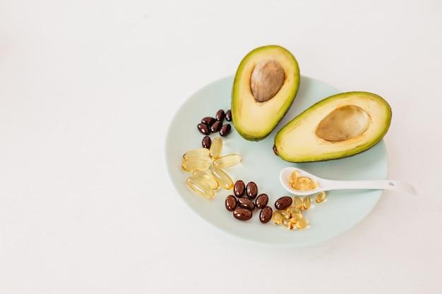 건강 관리 및 다이어트 개념입니다. 흰색 배경에 있는 접시에 있는 비타민 d와 오메가-3 지방산을 위한 캡슐에 들어 있는 아보카도와 생선 기름