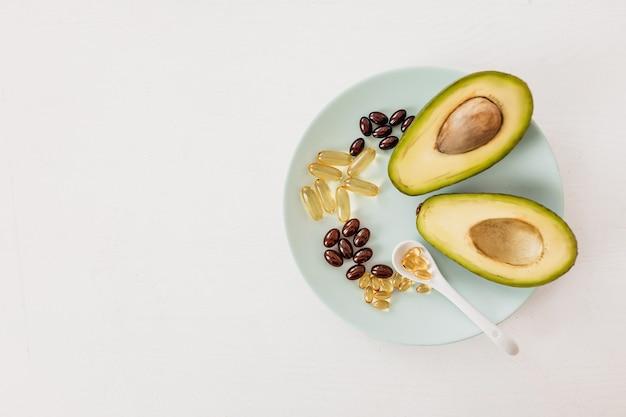 Концепция здравоохранения и диеты. авокадо и рыбий жир в капсулах для витамина d и жирных кислот омега-3 в тарелке на белом фоне