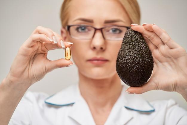건강 관리 및 다이어트 개념-비타민 d와 오메가 -3 지방산 및 아보카도 캡슐에 생선 기름을 들고 의사 영양사 또는 심장 전문의