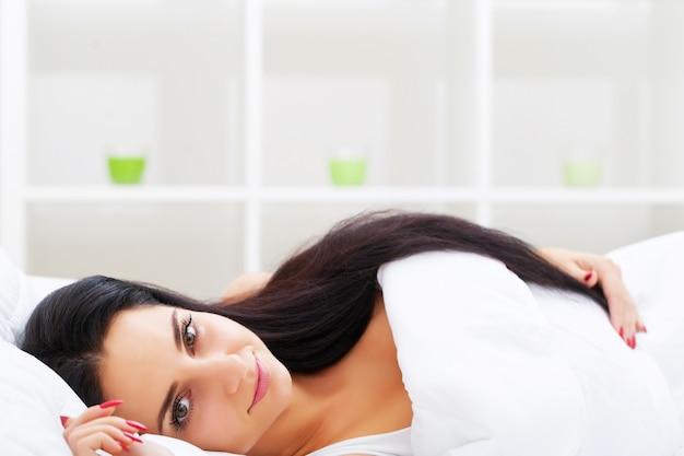 Здравоохранение. крупным планом красивая больная женщина с головной болью, болью в горле и лихорадкой, покрытые одеялом, чувствуя себя больным, измеряя температуру тела с помощью термометра. болезнь и недомогание. высокое разрешение