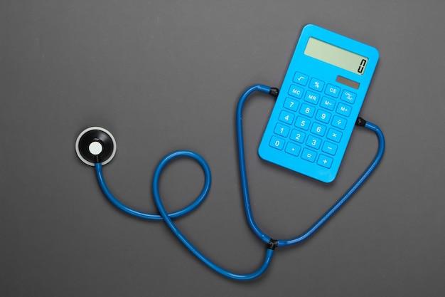 ヘルスケアの概念。灰色の聴診器を備えた電卓