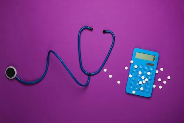 ヘルスケアの概念。聴診器付き電卓、紫色の錠剤