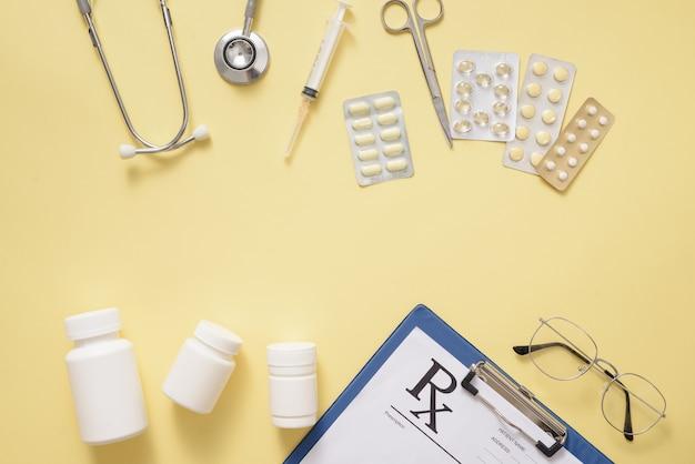 ヘルスケアの概念。黄色の背景にピルと医療用品を含む組成
