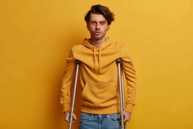 Health care concept. disabled man with crutches being handicapped after tragic accident, has bruises and abrasion, disable to walk, isolated over yellow wall. mobility assistance. injured male