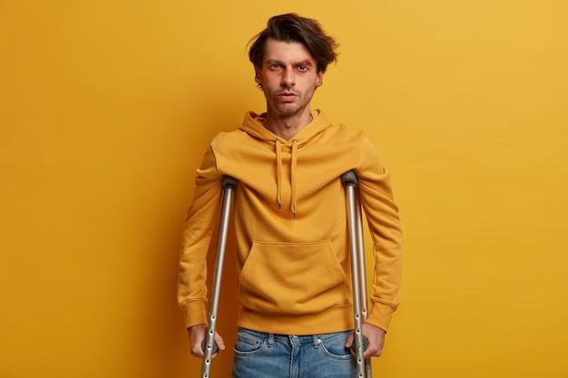 ヘルスケアの概念。悲劇的な事故の後に松葉杖で障害を負った障害者の男性は、打撲傷と擦り傷があり、歩くことができず、黄色い壁に隔離されています。モビリティ支援。負傷した男性