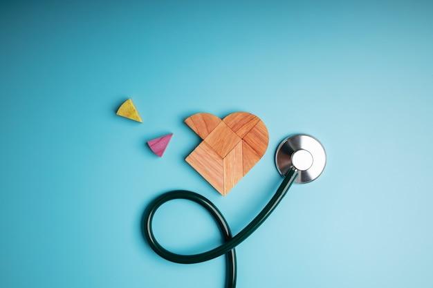 Концепция здравоохранения. международный день сердца. деревянная головоломка в форме сердца со стетоскопом