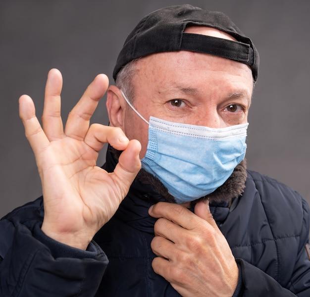 ヘルスケアの概念。灰色の背景の上のスタジオでポーズをとる保護マスクの年配の男性。 okサインのジェスチャー