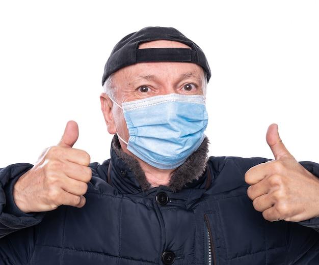 ヘルスケアの概念。白い背景の上のスタジオでポーズをとって保護マスクの年配の男性。 okサインのジェスチャー
