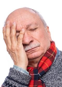 Концепция здравоохранения. старший мужчина страдает от головной боли на белом фоне