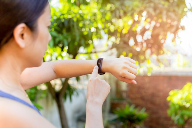 Health care concept woman checking fitness bracelet monitor on smart watch