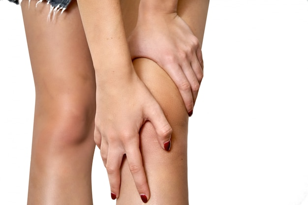 Health care concept. woman suffering from pain in knee. holding hands on the knee. isolated