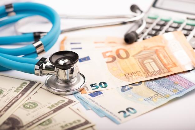 医療費。聴診器と医療費または医療保険のユーロ紙幣のクローズアップ
