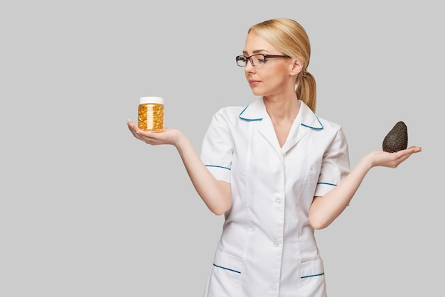 Health care and diet concept - doctor nutritionist or cardiologist holding fish oil in capsules for vitamin d and omega-3 fatty acids and avocado