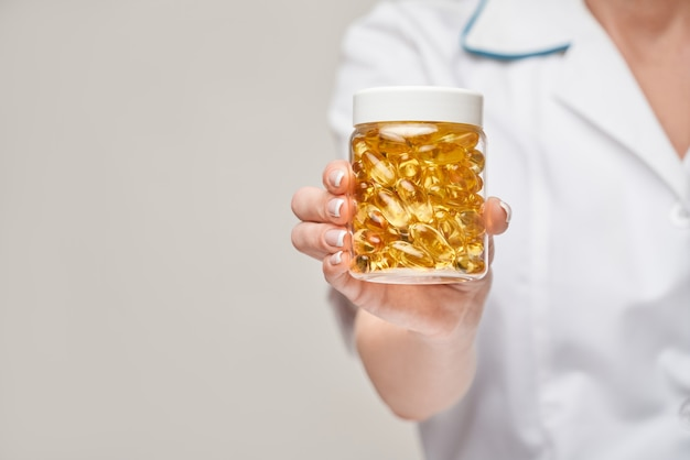 Health care and diet concept - doctor nutritionist or cardiologist holding fish oil in capsules for vitamin d and omega-3 fatty acids