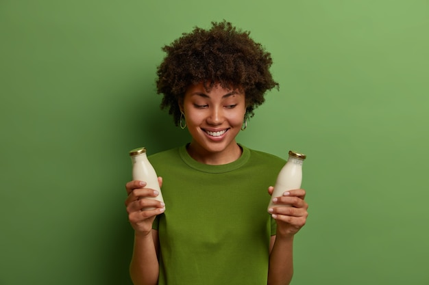 Health care, diet and nutrition concept. positive dark skinned young woman poses with organic vegan non diary milk, lactose free beverage, smiles pleasantly, wears green t shirt, poses indoor