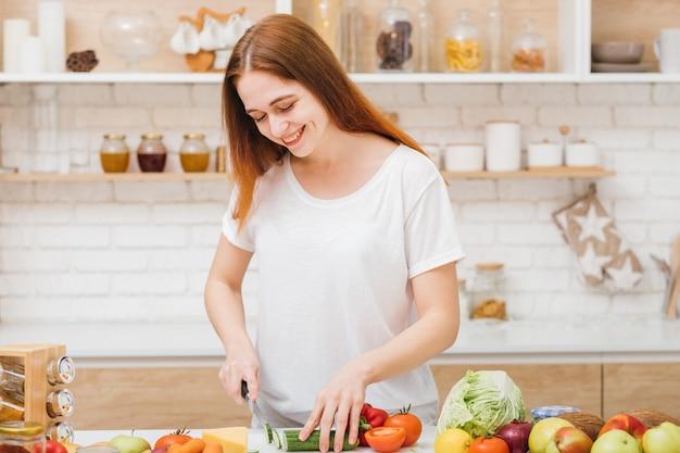 보건 의료. 잘 먹으십시오. 건강한 균형 잡힌 영양. 젊은 여성 자르고 야채 웃고.