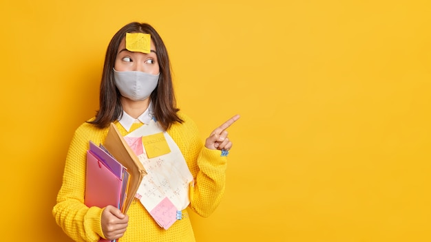 Health care and education concept. pleased teen student wears protective mask against coronavirus points on blank yellow wall demonstrates results of her project surrounded with papers sticky notes