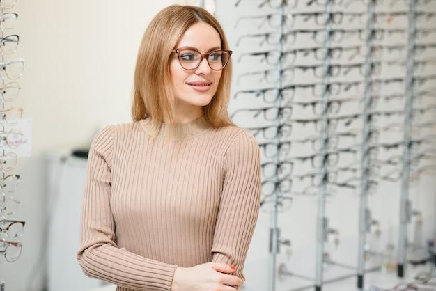 Здравоохранение, зрение и концепция зрения - счастливая женщина, выбирая очки в магазине оптики. портрет красивой молодой женщины пробует новые очки в магазине оптики