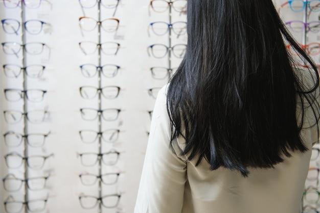 Концепция здравоохранения, зрения и зрения - счастливая женщина, выбирая очки в магазине оптики