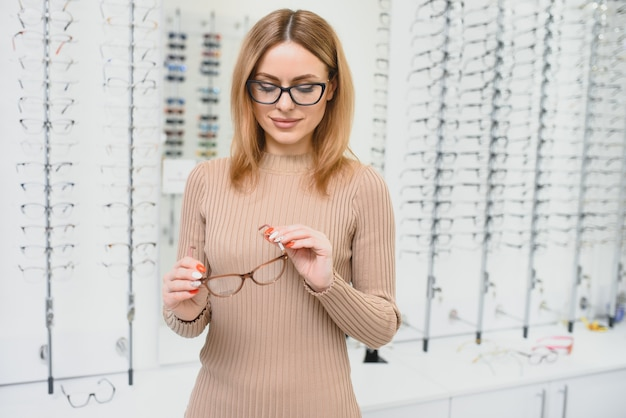 Health care, eyesight and vision concept - happy woman choosing glasses at optics store. portrait of beautiful young woman trying new glasses in optician store