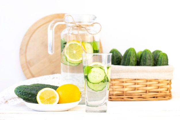 Health care, fitness, healthy eating concept. fresh cool lemon cucumber drink with water, cocktail, detox drink, lemonade in a glass jug and a glass. cucumbers and lemon on a plate