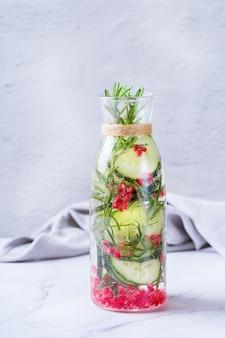 건강 관리, 피트니스, 건강한 영양 다이어트 개념. 신선한 시원한 오이 석류 로즈마리 주입 물, 해독 음료, 봄 여름날 유리병에 든 레모네이드. 공간 배경 복사