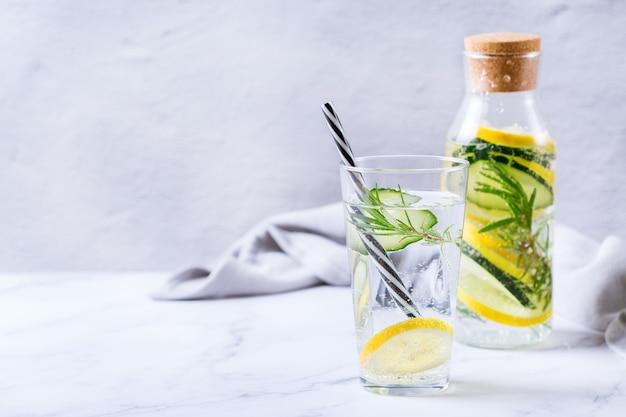 건강 관리, 피트니스, 건강한 영양 다이어트 개념. 신선한 시원한 레몬 오이 로즈마리 주입 물, 해독 음료, 봄 여름날 유리병에 든 레모네이드. 공간 배경 복사
