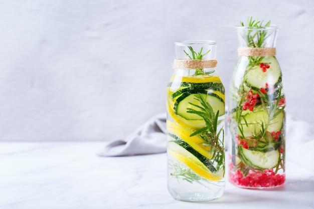 건강 관리, 피트니스, 건강한 영양 다이어트 개념. 신선한 시원한 레몬 오이 로즈마리 석류 주입 물, 해독 음료, 봄 여름날 유리병에 담긴 레모네이드. 공간 배경 복사