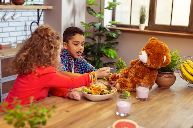 Health care. hungry international boy sitting near his friend and eating healthy food