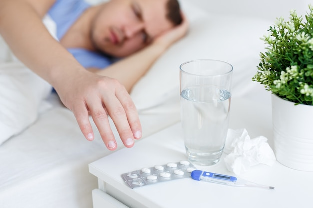 Health care and illness concept - sick man with fever taking pills from bedside table at home