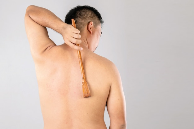 Health care or itchy or tinea cruris concept : portrait of people using scratch wood stick to scratching on his back side.