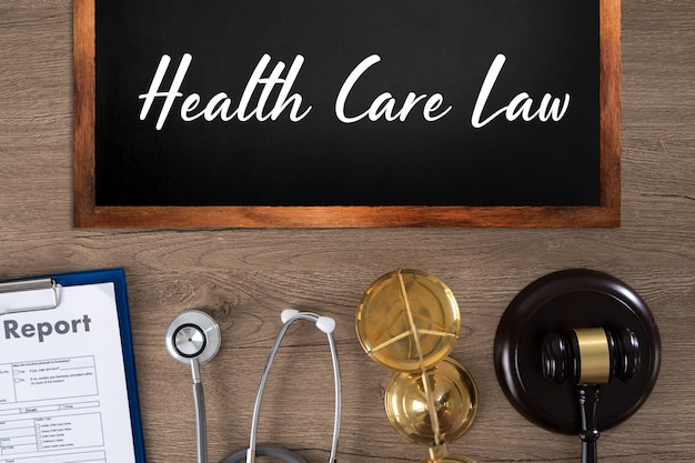 Health care law inscription on blackboard, report, stethoscope, scales and gavel