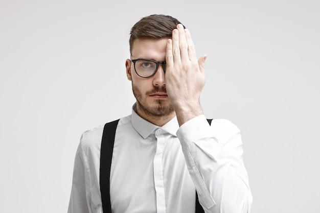 Concetto di assistenza sanitaria, medicina, persone, vista, ottica, occhiali e lenti a contatto. giovane serio con la stoppia che copre un occhio mentre si fa testare gli occhi durante l'esame della vista
