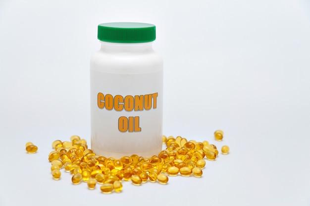 ヘルスケア-栄養補助食品-前面に散在する金のゲルカプセルが付いたココナッツオイルのボトル。