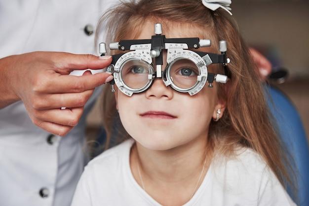 Забота о здоровье глаз. доктор проверяет зрение маленькой девочки и настраивает фороптер.